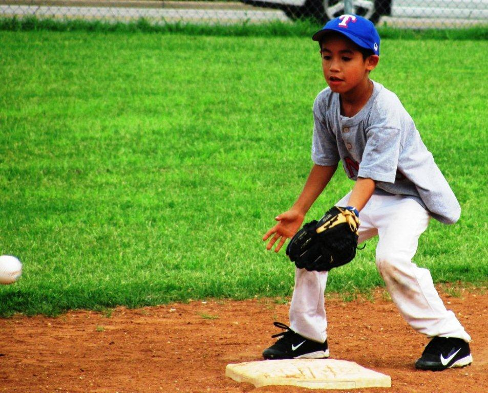 Boy standing at base catching the ball